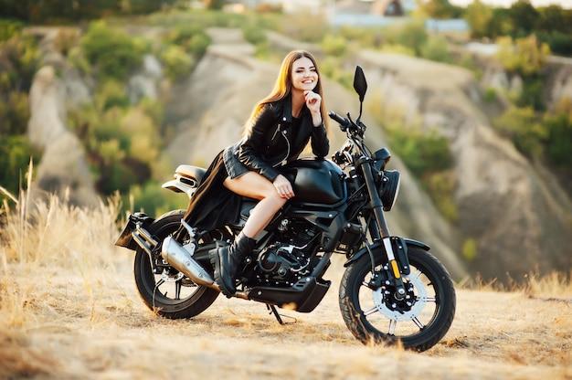 Mädchen auf einem motorrad. sie ist wunderschön und posiert bei sonnenuntergang auf einem motorrad.