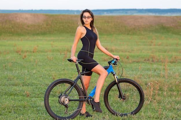 Mädchen auf einem mountainbike auf einem feld