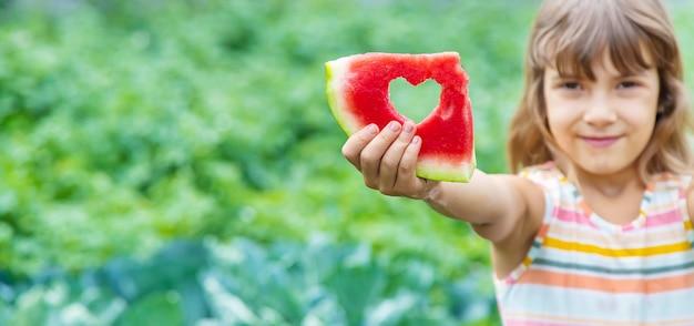Mädchen auf einem picknick isst eine wassermelone.