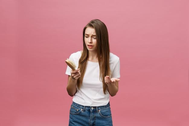 Mädchen auf einem rosa hintergrund mit einem kamm für das haar, das haarproblem