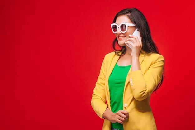 Mädchen auf einem roten hintergrund in einer gelben jacke, die am telefon spricht. speicherplatz kopieren