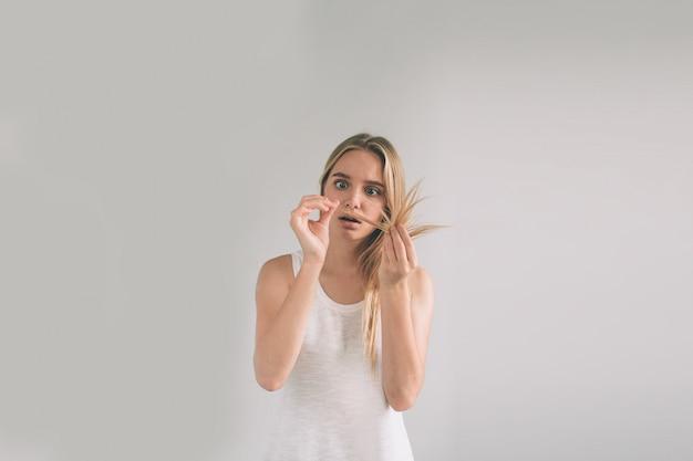Mädchen auf einem weißen hintergrund mit einem haarproblem. blonde frau trägt hemd isoliert auf weiß.