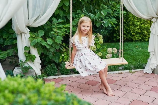 Mädchen auf einer schaukel im sommer im garten