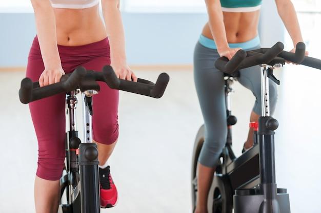 Mädchen auf heimtrainern. abgeschnittenes bild von zwei jungen frauen in sportkleidung