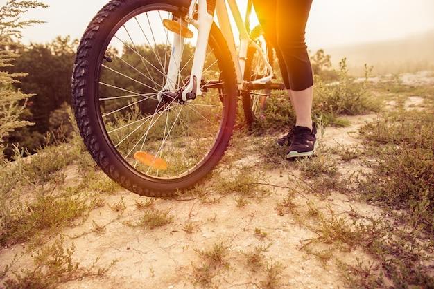 Mädchen auf mountainbiketouren auf dem weg auf einem schönen sonnenaufgang. fahrradrad nahaufnahme