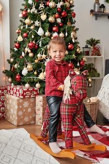Mädchen auf schaukelpferd nahe weihnachtsbaum weihnachten im kinderzimmer. lustiges babylügen. süßes kleines baby.
