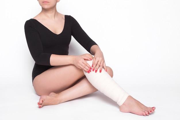 Mädchen auf weiß korrigiert einen elastischen verband, der bindet