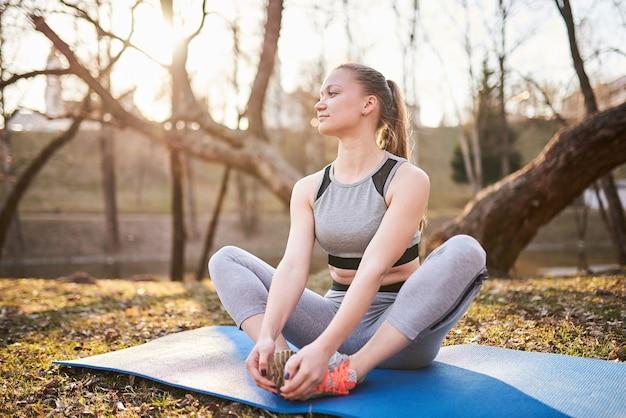 Mädchen auf yogamatte im park