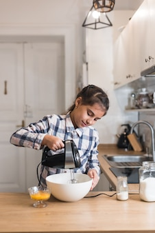Mädchen backt und mischt teig für haferkekse mit pflaumen. weibliches kind, das teig mit mischer oder mixer knetet. hausgemachtes essen.