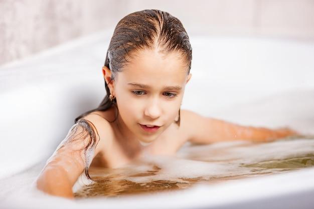 Mädchen badet in einer badewanne mit schaum und hat spaß während der quarantäne zu hause