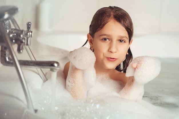 Mädchen badet und spielt mit schaum im badezimmer.