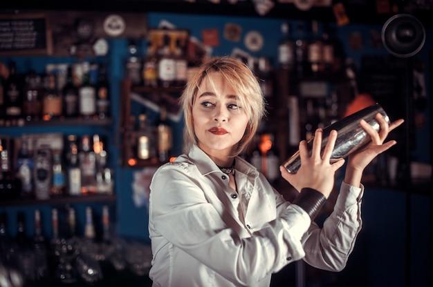 Mädchen bardame kocht einen cocktail in der brasserie