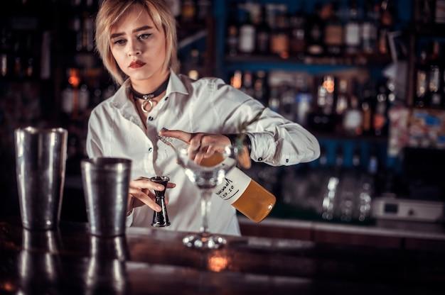 Mädchen barkeeper kreiert einen cocktail auf dem öffentlichen haus