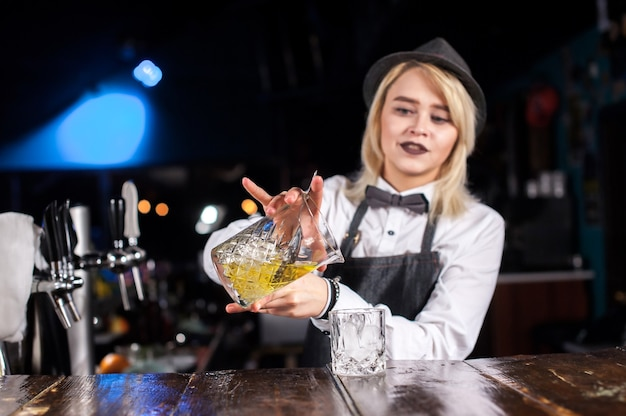 Mädchen barkeeper kreiert einen cocktail im öffentlichen haus