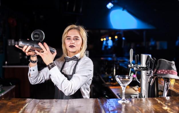 Mädchen barkeeper macht einen cocktail im schlaghaus