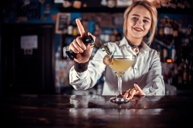 Mädchen barmann formuliert einen cocktail im schankraum