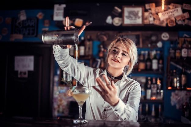 Mädchen barmann formuliert einen cocktail in der brasserie
