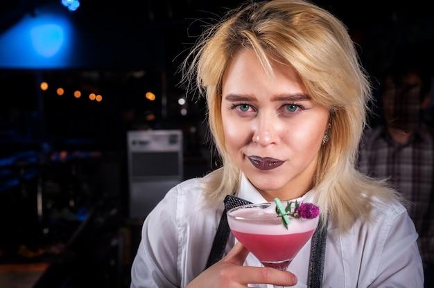 Mädchen barmann kocht einen cocktail hinter der bar