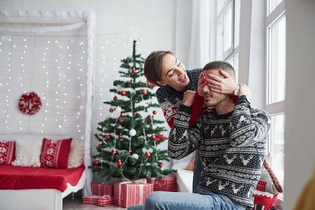 Mädchen bedeckt die augen des mannes mit ihren händen, um ihm ein geschenk zu machen. glückliche junge leute sitzen auf der fensterbank im zimmer mit weihnachtsdekoration.