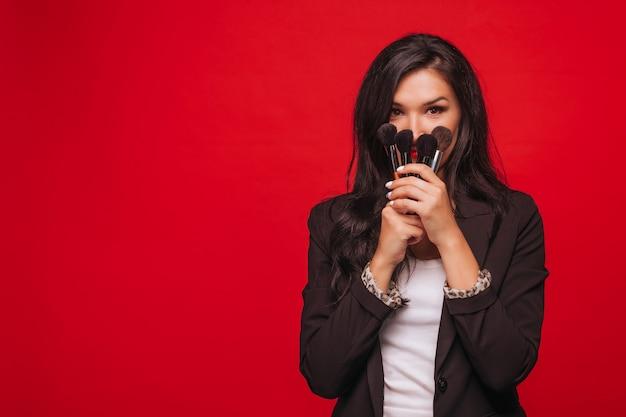 Mädchen bedeckt ihr gesicht mit make-up-pinseln auf rotem hintergrund