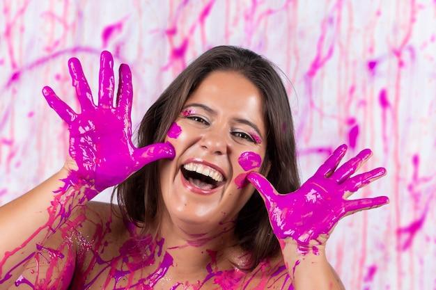 Mädchen bedeckt mit rosa farbe, die spaß hat und frei ist, auf einem konzept, das gegen brustkrebsbewusstsein und frauenbefreiung hilft.