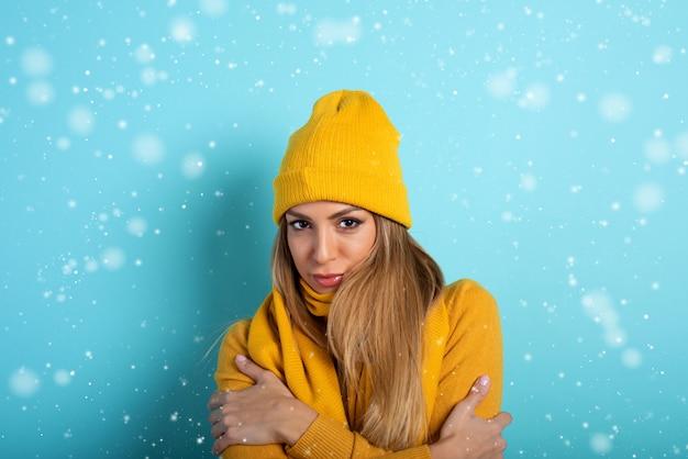 Mädchen bedeckt sich, um sich nicht zu erkälten. cyan hintergrund