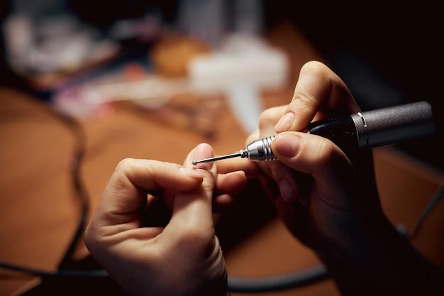 Mädchen behandelt nägel mit einem fräser für maniküre