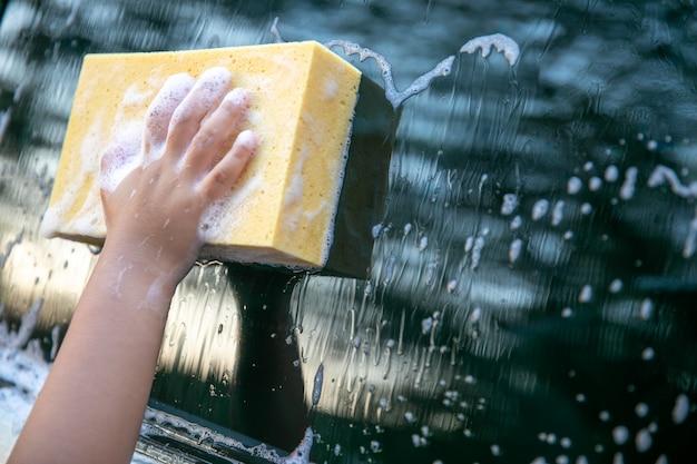 Mädchen benutzen autowaschschwamm