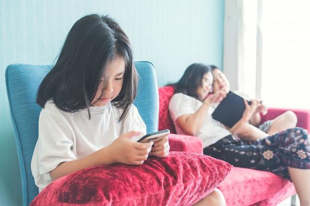 Mädchen benutzt einen smartphone auf stuhl mutter, die zu hause mit bruder auf sofa genießt