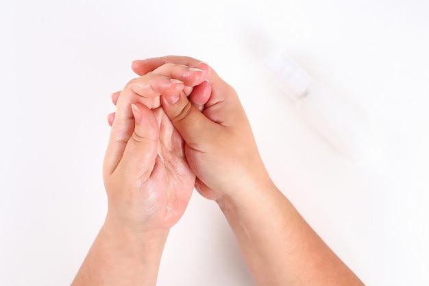 Mädchen benutzt handcreme auf weiß. ansicht von oben.