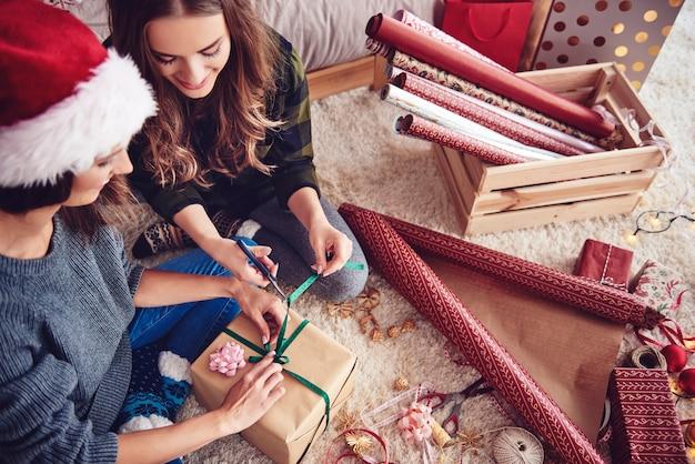 Mädchen bereiten ein geschenk für weihnachten vor