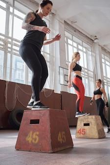 Mädchen bereiten sich auf den sommer vor. junge sportliche kaukasische frauen, die sprungübungen mit ausrüstung in der geräumigen sporthalle, niedrige winkelansicht tun