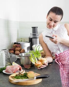 Mädchen bereitet essen in der küche mit dem telefon