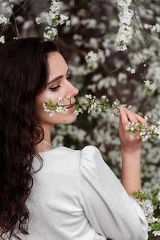 Mädchen berührt und schnüffelt einen zweig eines weißen blühenden baumes ohne medizinische maske. frühlingsspaziergang im park.