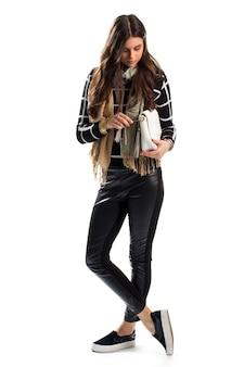 Mädchen berührt weiße handtasche. sweatshirt und beiger schal. trendige slipper. lederhose mit seitlichen einsätzen.