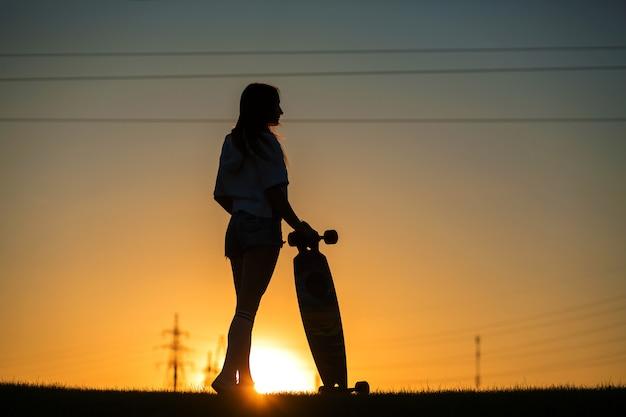 Mädchen betrachtet den sonnenuntergang, der ein longboard in ihrer hand hält
