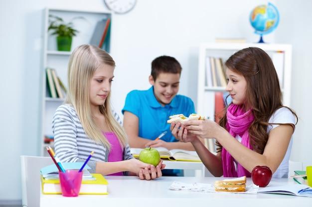 Mädchen bietet sandwich zu ihrem freund