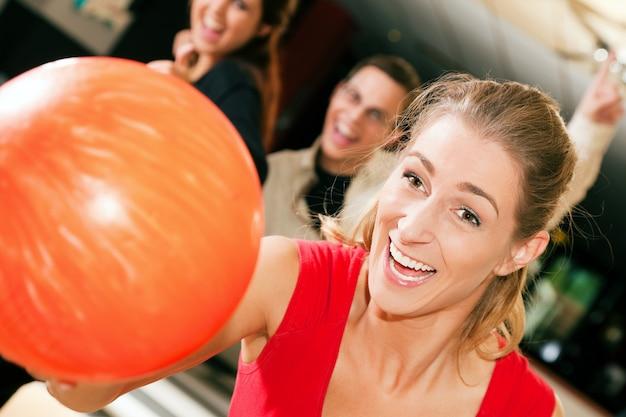Mädchen bowling mit freunden