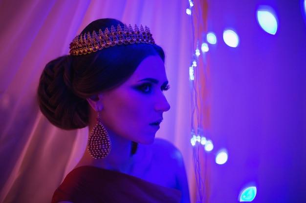 Mädchen brunette in einem roten kleid mit schöner frisur, ohrringen von perlen und einer krone auf ihrem kopf und hellem make-up. weiblicher stil. mysteriöse frau. blaues licht
