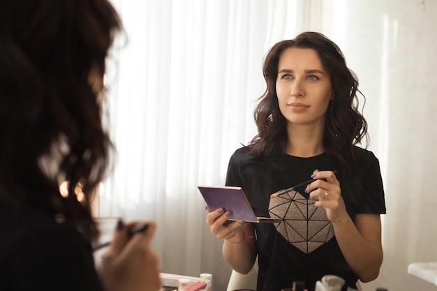 Mädchen brunette setzt make-up vor den spiegel, reflexion in den spiegel