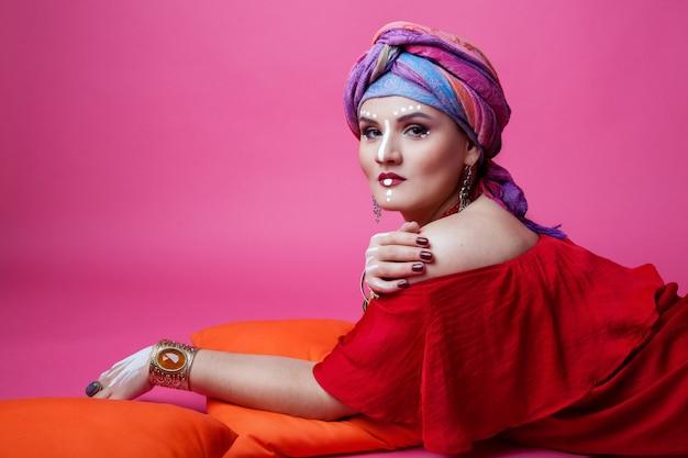 Mädchen brunettemodell plus die größe, die auf einem rosa hintergrund in der ethnischen kleidung und im make-up aufwerfend liegt