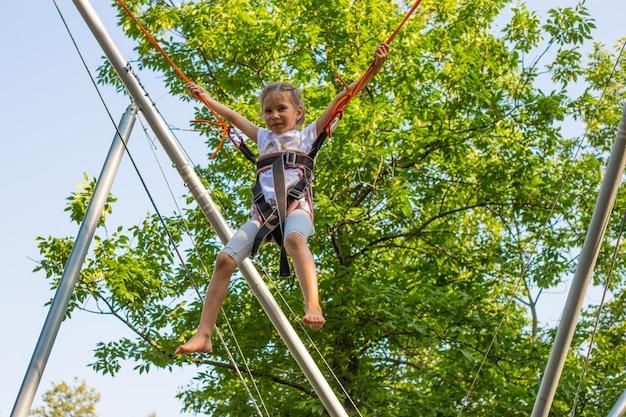 Mädchen bungee springen im trampolin mit einer guten zeit