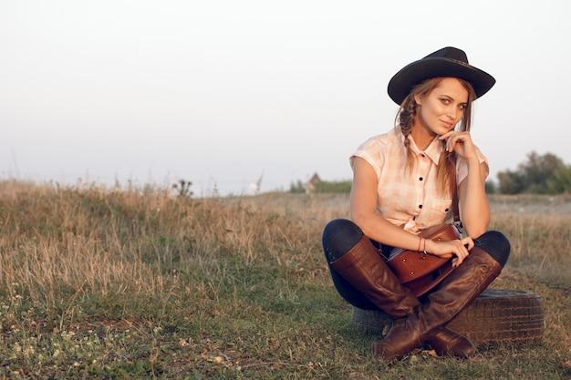 Mädchen cowgirl in jeans stiefel hemd und mit einer tasche in einer box mit einem rad von einem baum