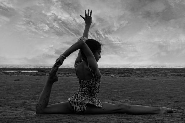Mädchen, das akrobatische bewegungen am strand durchführt