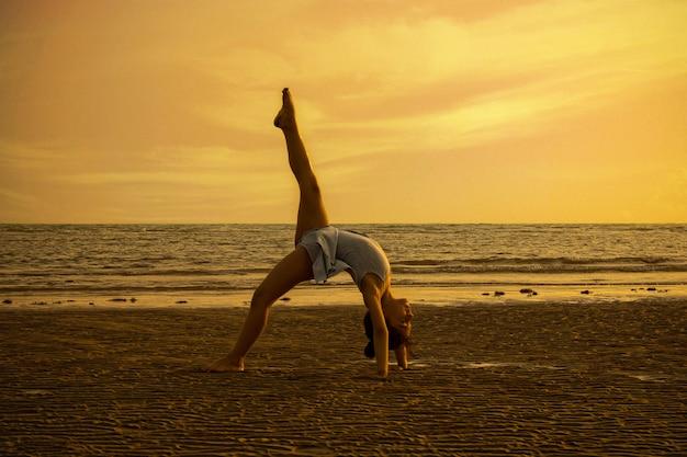 Mädchen, das akrobatische bewegungen am strand im sonnenuntergang durchführt