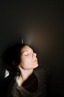 Mädchen, das allein in der sonnenlichttasche im dunklen raum sitzt. konzept der psychischen gesundheit