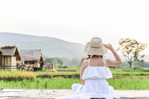 Mädchen, das alleine auf balkon sitzt und das berg- und reisfeld betrachtet