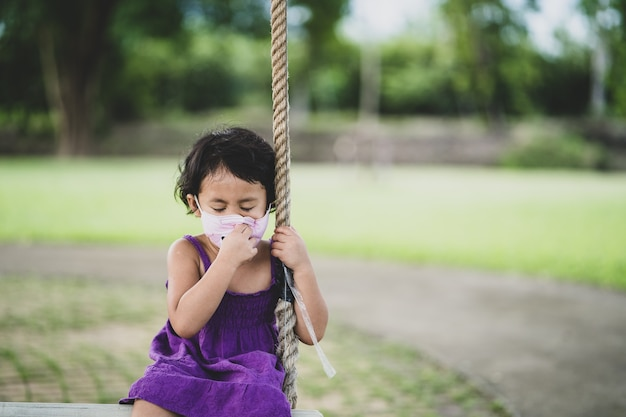 Mädchen, das allergisch auf eine schützende gesichtsmaske ist, die im freien sitzt hautreizung