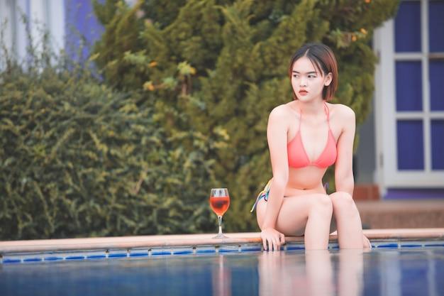 Mädchen, das am pool sich entspannt asiatische junge weibliche person, die im poolbadekurort genießt