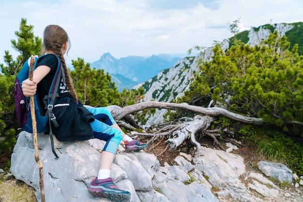 Mädchen, das am schönen sommertag in den alpenbergen wandert